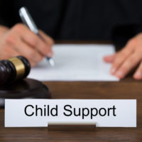 Attorney at desk with child support sign on it