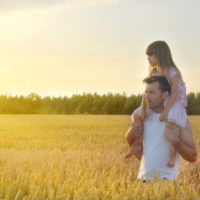 Father takes his daughter in wheat field
