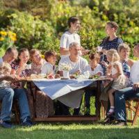 big family eats by their garden