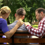 parents support teenage child on bench in park