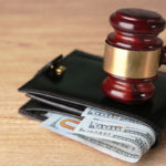 gavel on top of money with wallet for garnishment concept