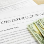 life insurance policy document with hundred dollar bills