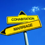 Cohabitation vs Marriage - Traffic sign with two options - unofficial couple living together vs married wife and husband as official partners
