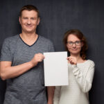 Portrait of couple holding white blank paper sheet together