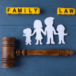 Flat lay composition with figure and gavel on blue wooden background. Family law concept