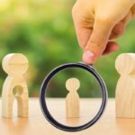 A magnifying glass looks at a child's figure stands between father and mother. The child chooses which parent to live with after their divorce. Guardianship over child. interest of child