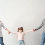 Divorced parents arguing about child custody on light background
