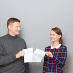 Studio shot of adult couple holding and tearing paper sheet