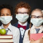 Children in protective face mask on black background, back to school and covid-19 concept