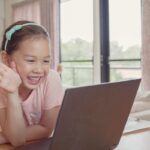 Asian girl making facetime video calling with laptop, using zoom learning online app, home based remotely learning social distancing, isolation, homeschooling education, learning remotely, new normal