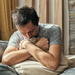 Depressed man sitting on living room sofa and hugging pillow