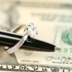 Wedding ring on pen, on banknotes background. Marriage of convenience