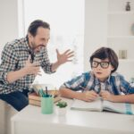 Photo of aggressive dad screaming at his small son who does not understand the material and home task he is very terrified sitting at the table trying to concentrate read textbook