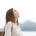 Happy woman on the beach breathing fresh air