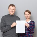 Portrait of adult couple holding together white blank paper sheet